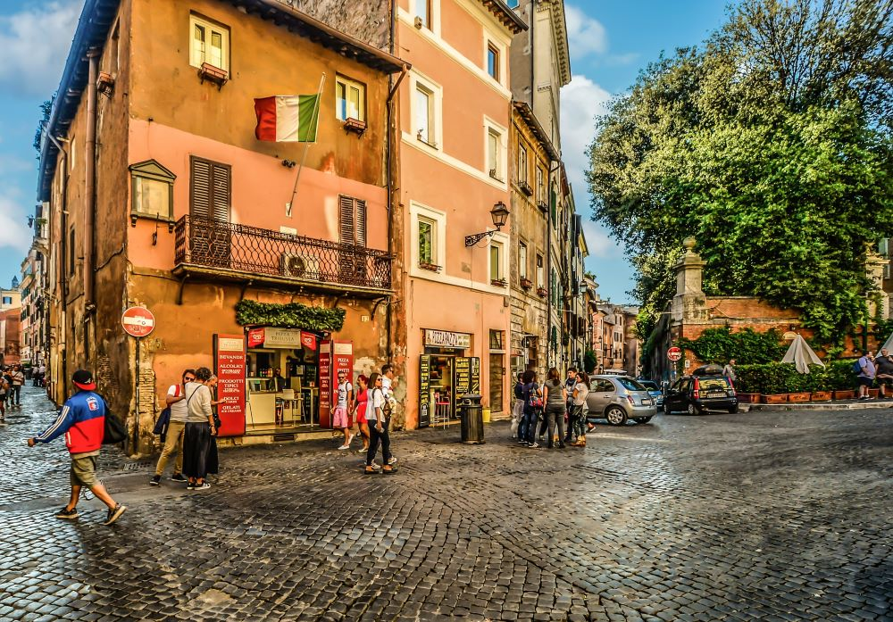 people standing, walking, and talking outside a small store somewhere in Rome Italy
