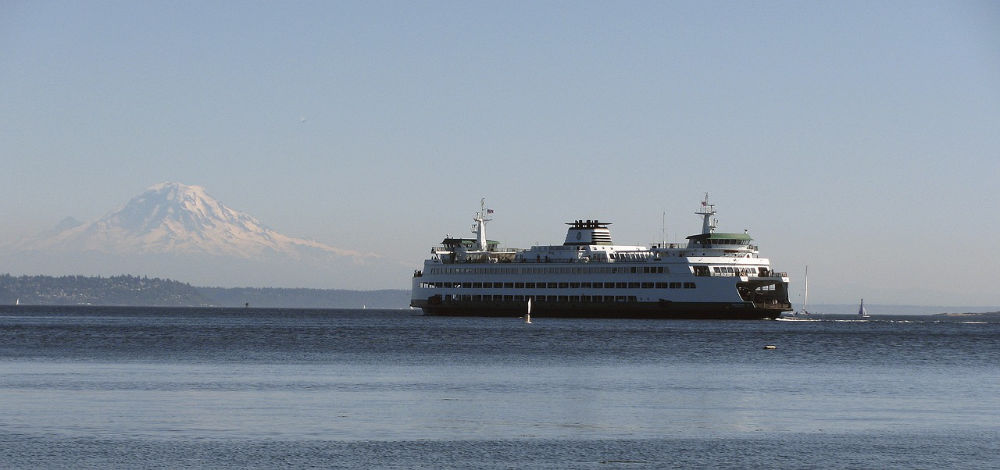 A ferry in the water in seattle washington with mount rainier in the background
