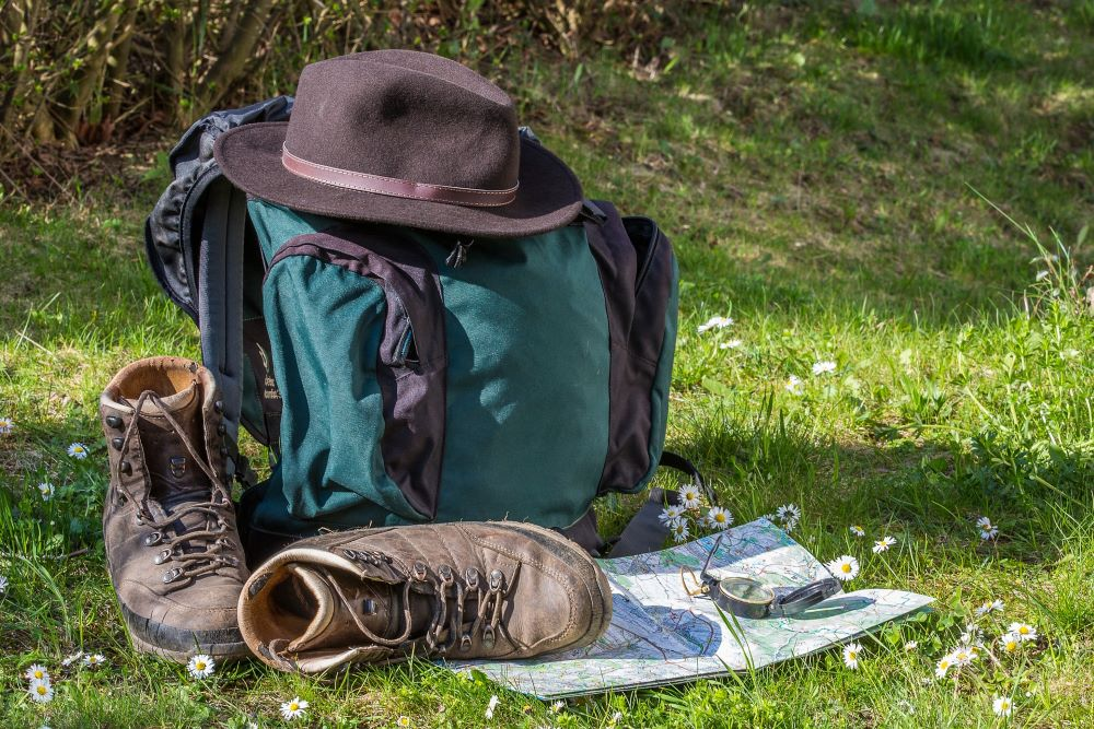 backpack sitting on a grass floor with essentials ready for a backpacking trip