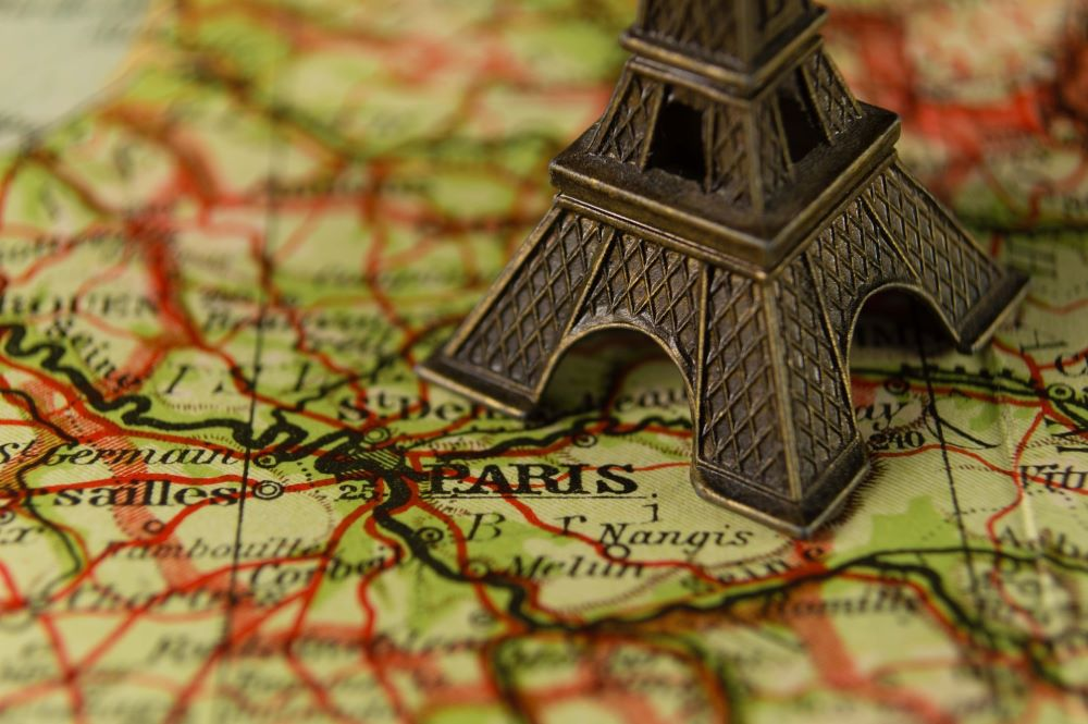 Road map showing Paris the capital city of France, with a metal eiffel tower sitting on top of it