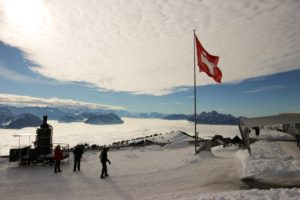 Three Person Standing on a snowy mountain next to a Switzerland flag