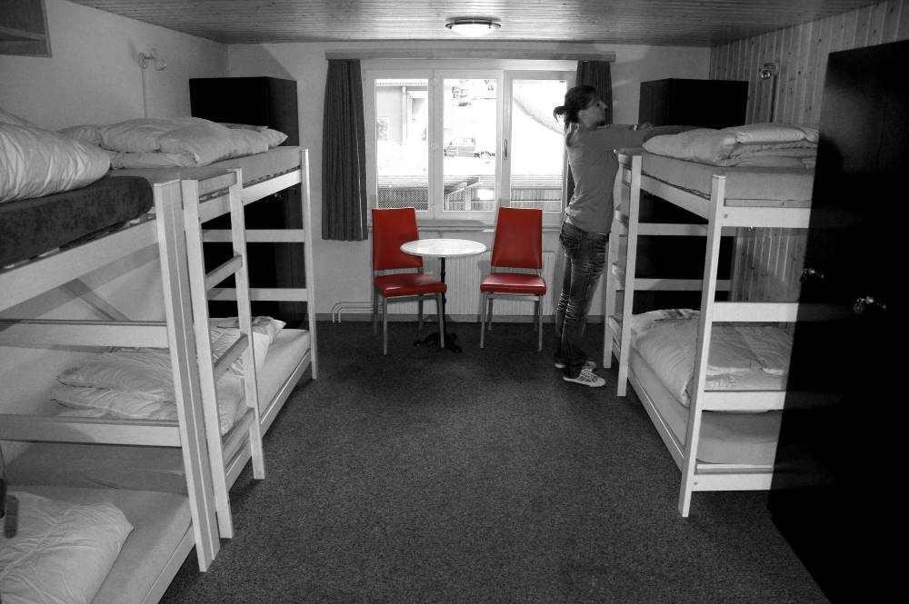 Woman wearing black pants and gray shirt, fixing beds at a hostel room